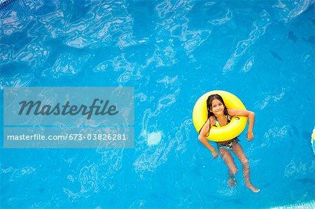girl in yellow life ring in pool