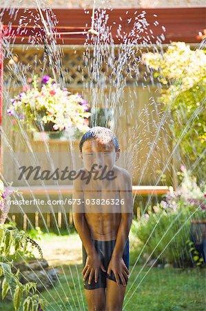 smiling boy standing in sprinkler
