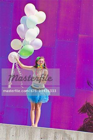 teen girl holding bunch of balloons