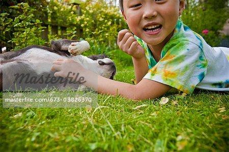 boy tickling dog's belly