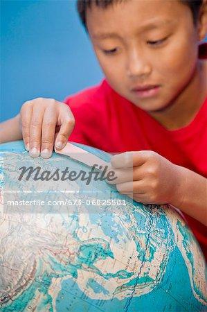 Boy placing bandaid on globe
