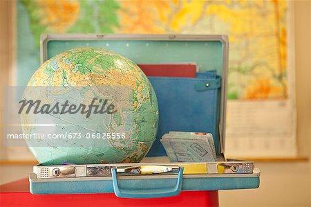 Globe sitting inside open vintage briefcase