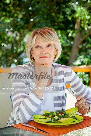 Woman eating salad outdoors