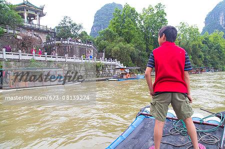 Boy standing on a bamboo raft on the Li River, Yangshuo, China