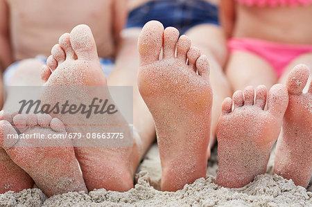 Family sitting on the beach, focus on bare feet.