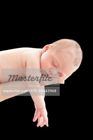 Person holding sleeping newborn baby boy, studio shot.