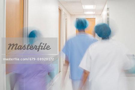 Medical staff walking down hospital corridor.
