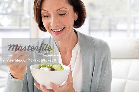 Mature woman eating salad.