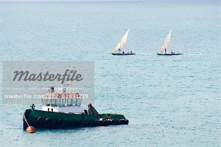 Tug boat with two mashua dhows in the background on a calm sea, Stone Town, Unguja Island, Zanzibar, Tanzania