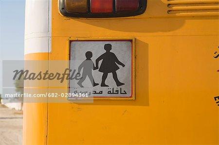 Arabic student crossing sign on yellow school bus