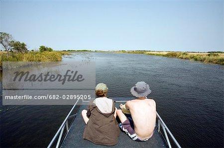 Rear view of two people on a boating trip on the Okavango River, Okavango Delta, Botswana