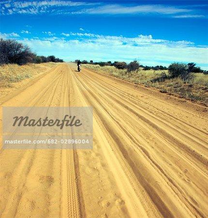 Biker driving on dirt road, Central Kalahari Desert, Botswana