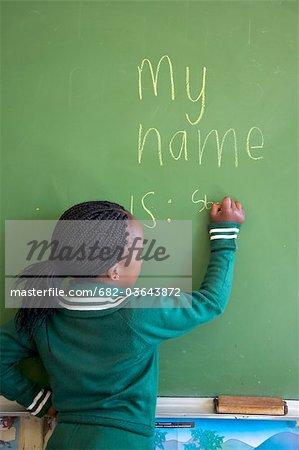 Young schoolgirl writes her name on the classroom chalkboard, KwaZulu Natal Province, South Africa