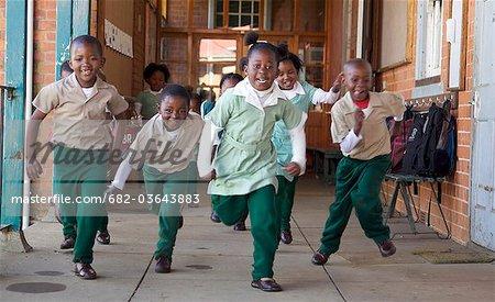 Group of schoolchildren running outside their classroom, KwaZulu Natal Province, South Africa