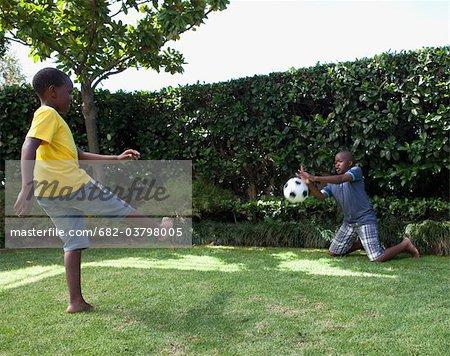 Children playing soccer in garden, Johannesburg, South Africa