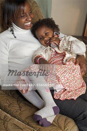 Teen girl with baby sister calling Mum, Nairobi, Kenya