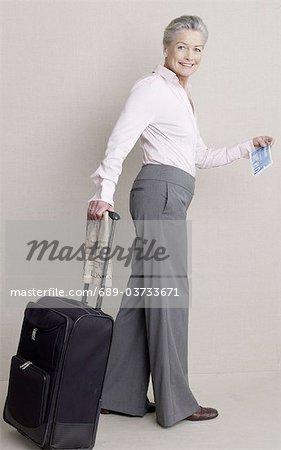 Senior woman pushing rolling suitcase