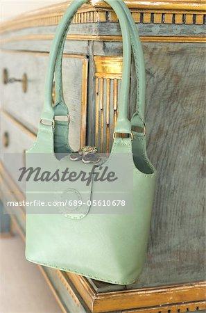 Green handbag hanging at sideboard