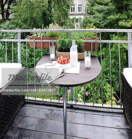 Milk, strawberries, eyeglasses and newspaper on balcony table