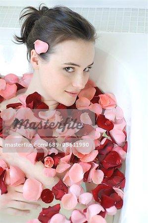 Young woman enjoying bath with rose petals