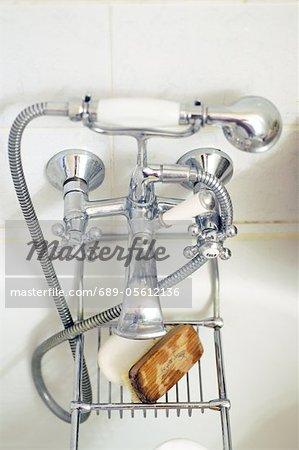 Water tap and nailbrush at bathtub