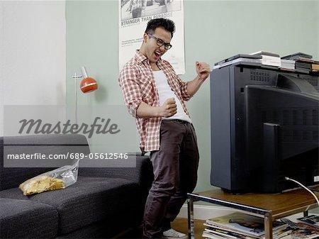Cheering man watching TV