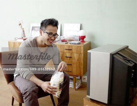 Smiling man watching TV