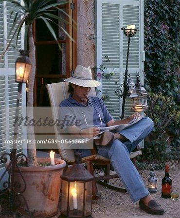 Man reading newspaper on terrace
