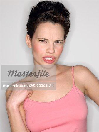 Woman gritting teeth in studio, half-length
