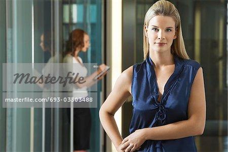Businesswoman standing in office corridor, portrait