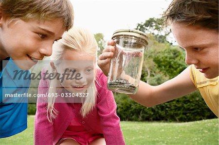 Children Looking at Snake in Jar