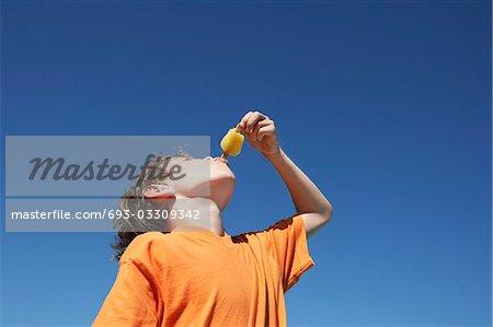 Boy (7-9) eating popsicle, blue sky