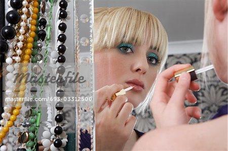 Teenage girl (16-17) looking in mirror and applying lip gloss