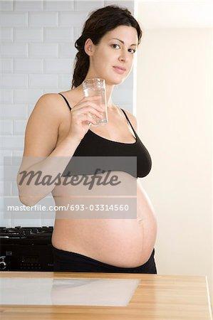 Pregnant woman drinking water in kitchen, portrait