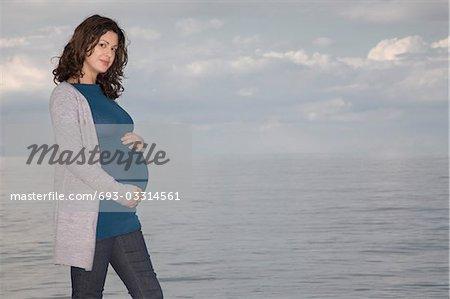 Pregnant woman at ocean, portrait