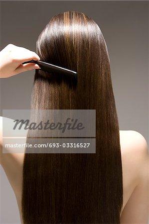 Woman combing long brown hair, rear view