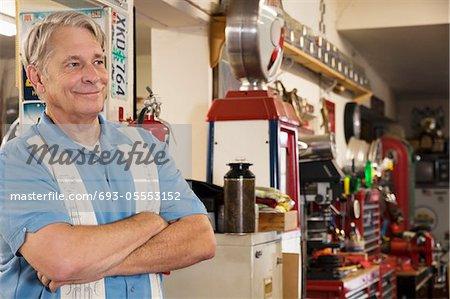 Smiling senior man in automobile workshop