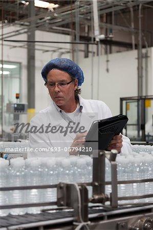 Man at bottling plant inspecting bottled water on conveyor