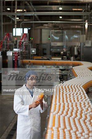 Worker inspecting orange juice bottle at bottling plant