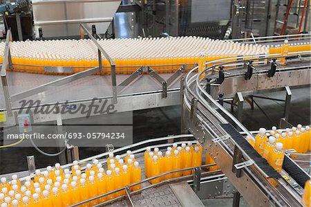 Orange juice bottles on conveyor belt in bottling plant