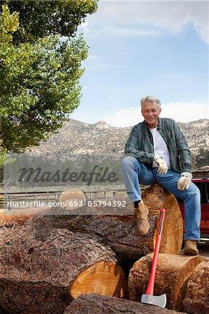 Man sitting on chopped tree trunk