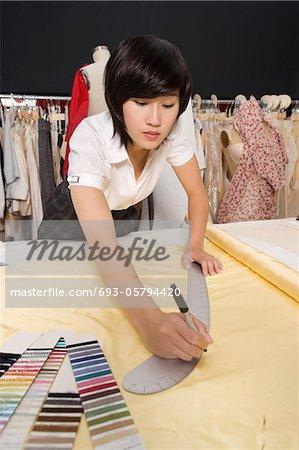 Female dressmaker measuring fabric
