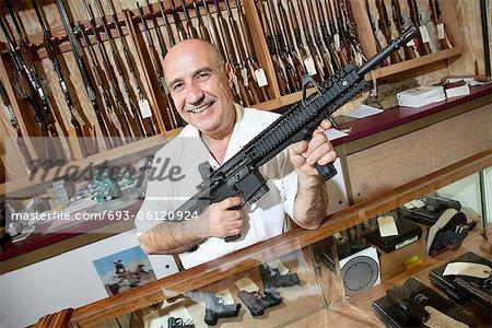 Portrait of a happy mature merchant with rifle in gun shop