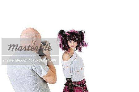 Senior photographer in shooting fashion model over white background