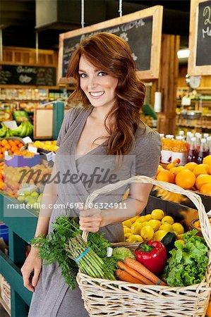 Portrait of beautiful brunette with basket shopping in market