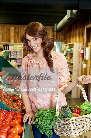 Portrait of beautiful brunette holding basket near tomato stall in market