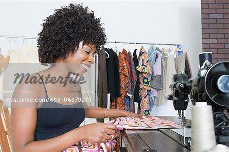 African American female dressmaker stitching cloth on sewing machine