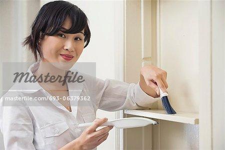 Portrait of female housekeeper cleaning shelf