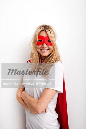 Portrait of confident woman in superhero costume against white background
