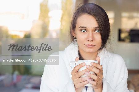 Sick young woman holding coffee mug at home